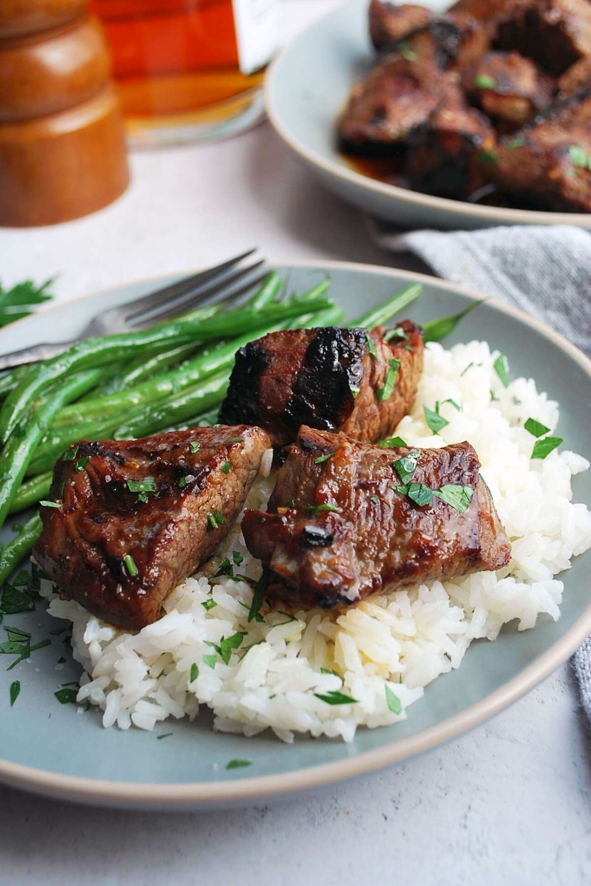 steak tips over a bed of rice with green beans
