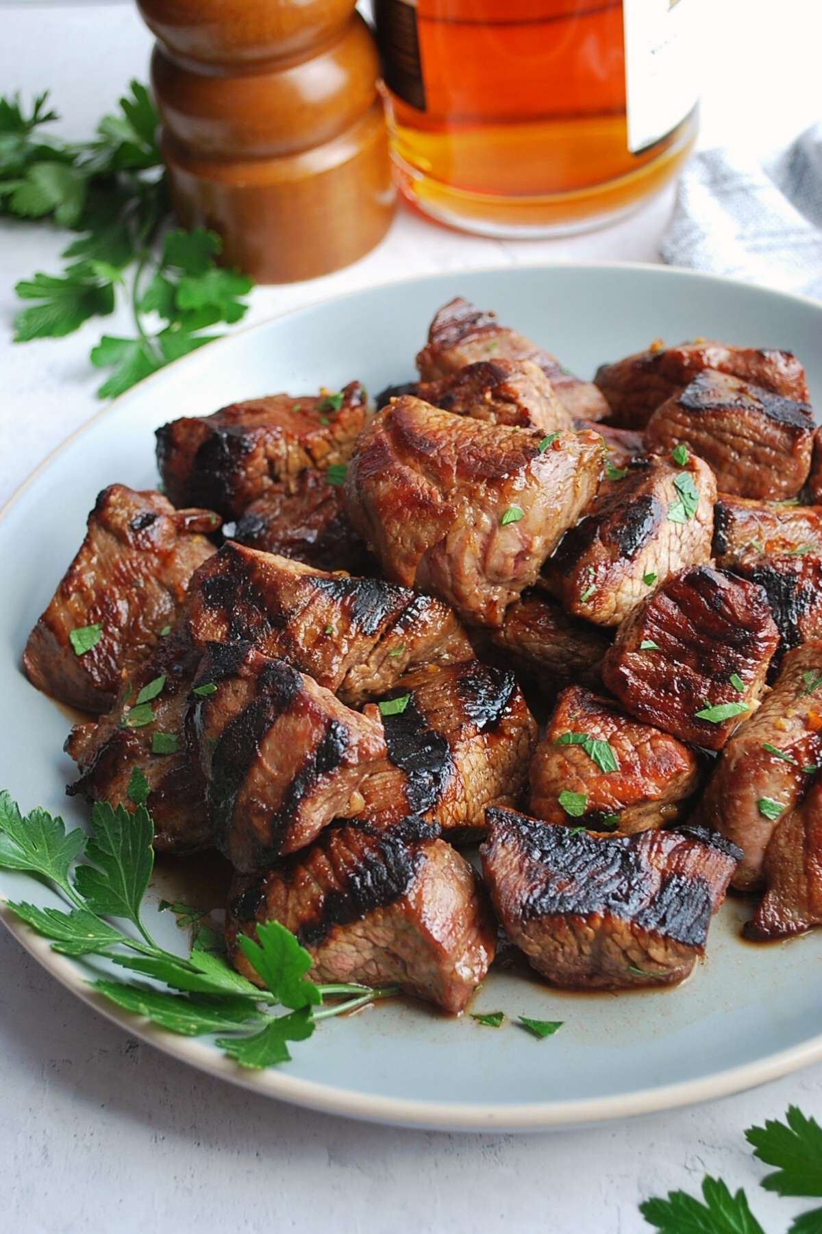 grilled beef tips on a plate with parsley