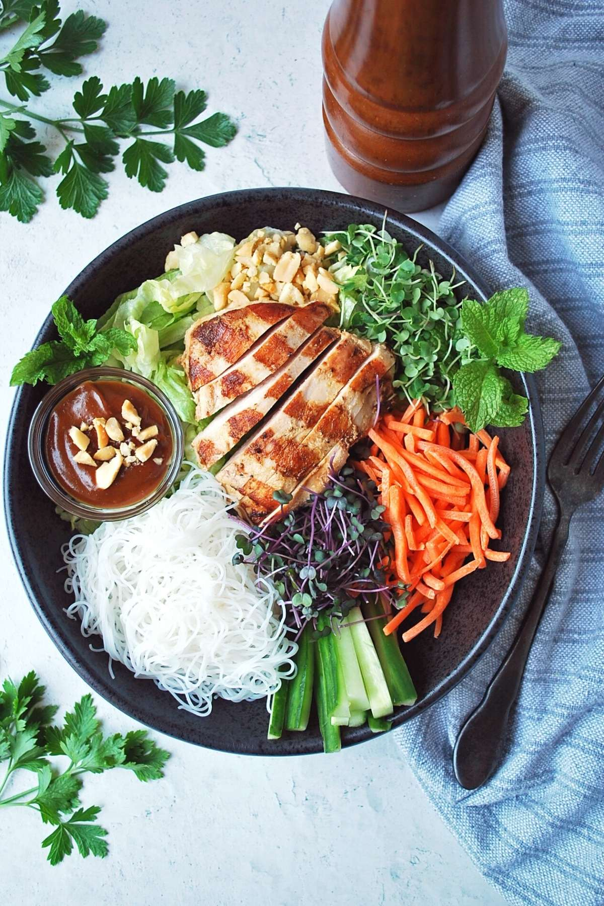 overhead photo of a grilled chicken spring roll salad with parsley and a spoon in the background