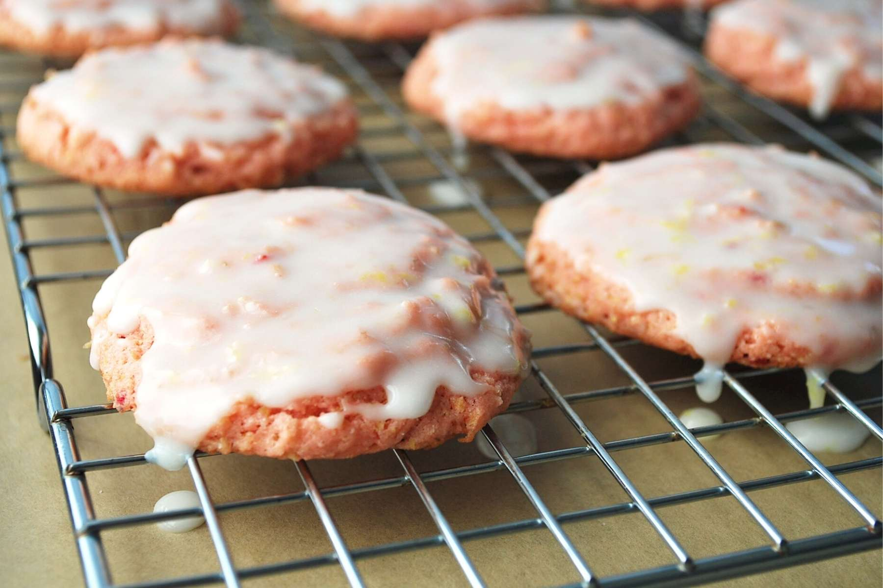 freshly glazed strawberry lemonade cookies on a cooling rack