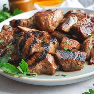 close up of steak tips on a gray plate with fresh parsley