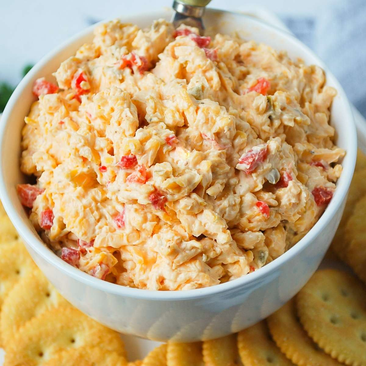 close up of jalapeno pimento cheese in a serving bowl with crackers