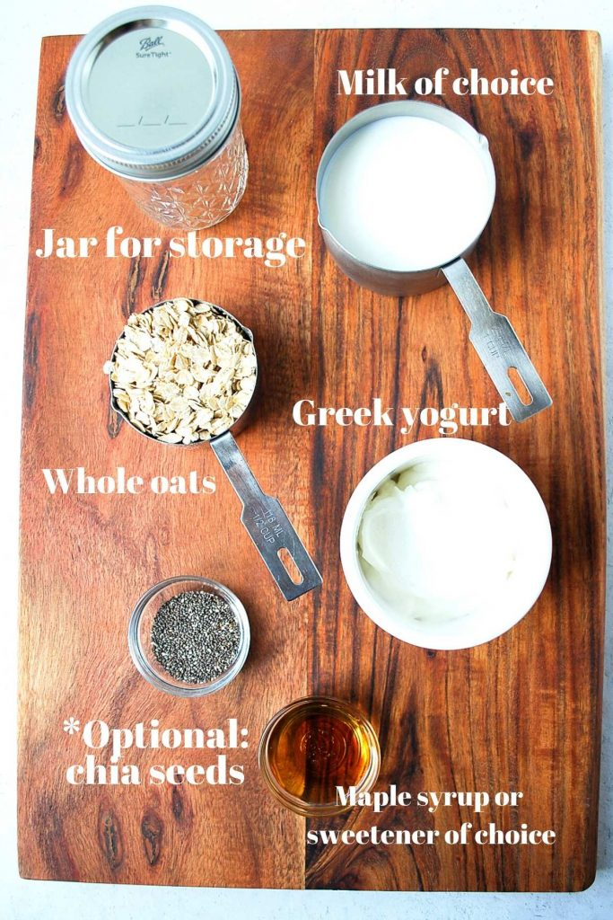Greek yogurt, chia seeds, oats, Mason jar, and milk on a wood backdrop