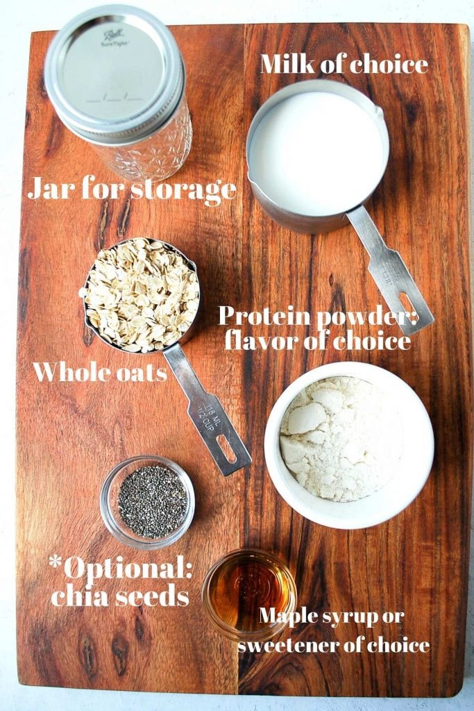 Protein powder, chia seeds, oats, Mason jar, and milk on a wood backdrop