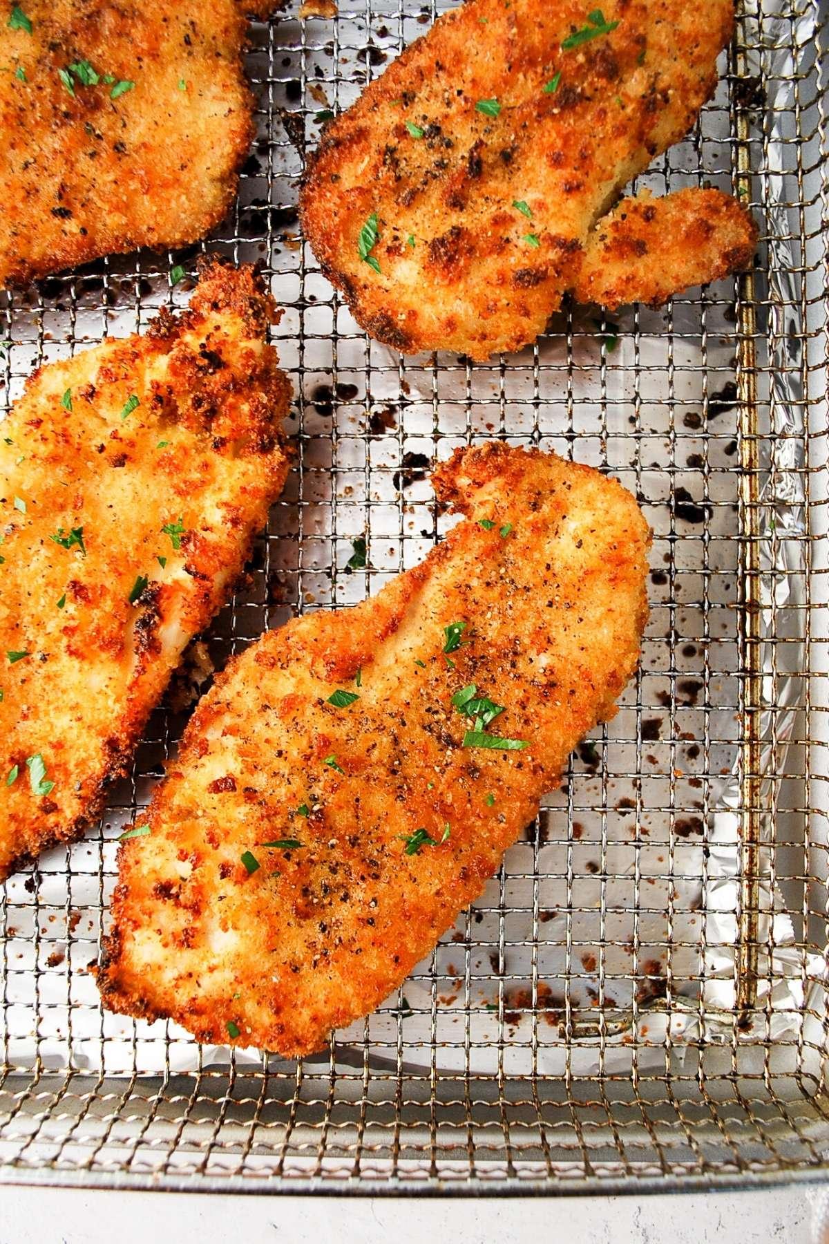 chicken cutlets on an air fryer baking sheet