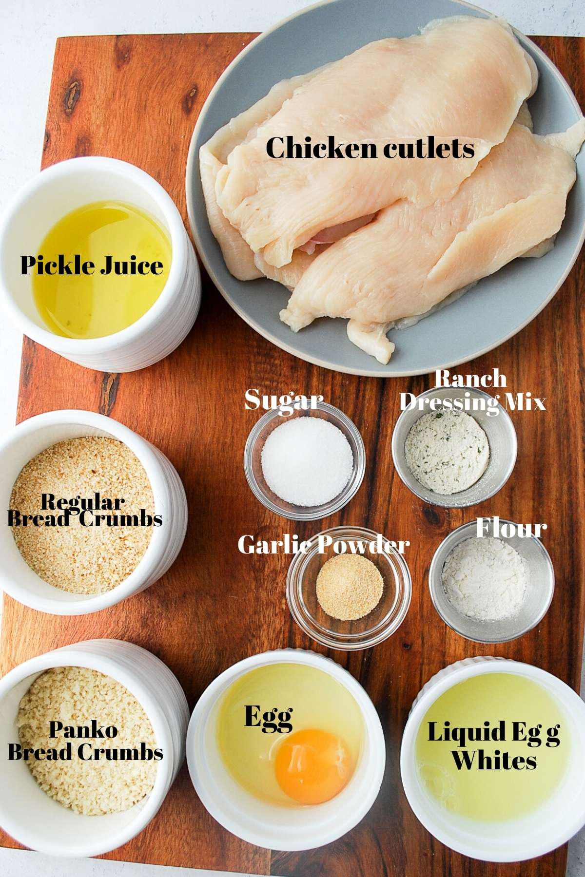 chicken cutlets, pickle juice, bread crumbs, egg, and seasonings for making air fried chicken cutlets on a wood board