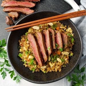 overhead photo of Asian flank steak bowls with chop sticks on top