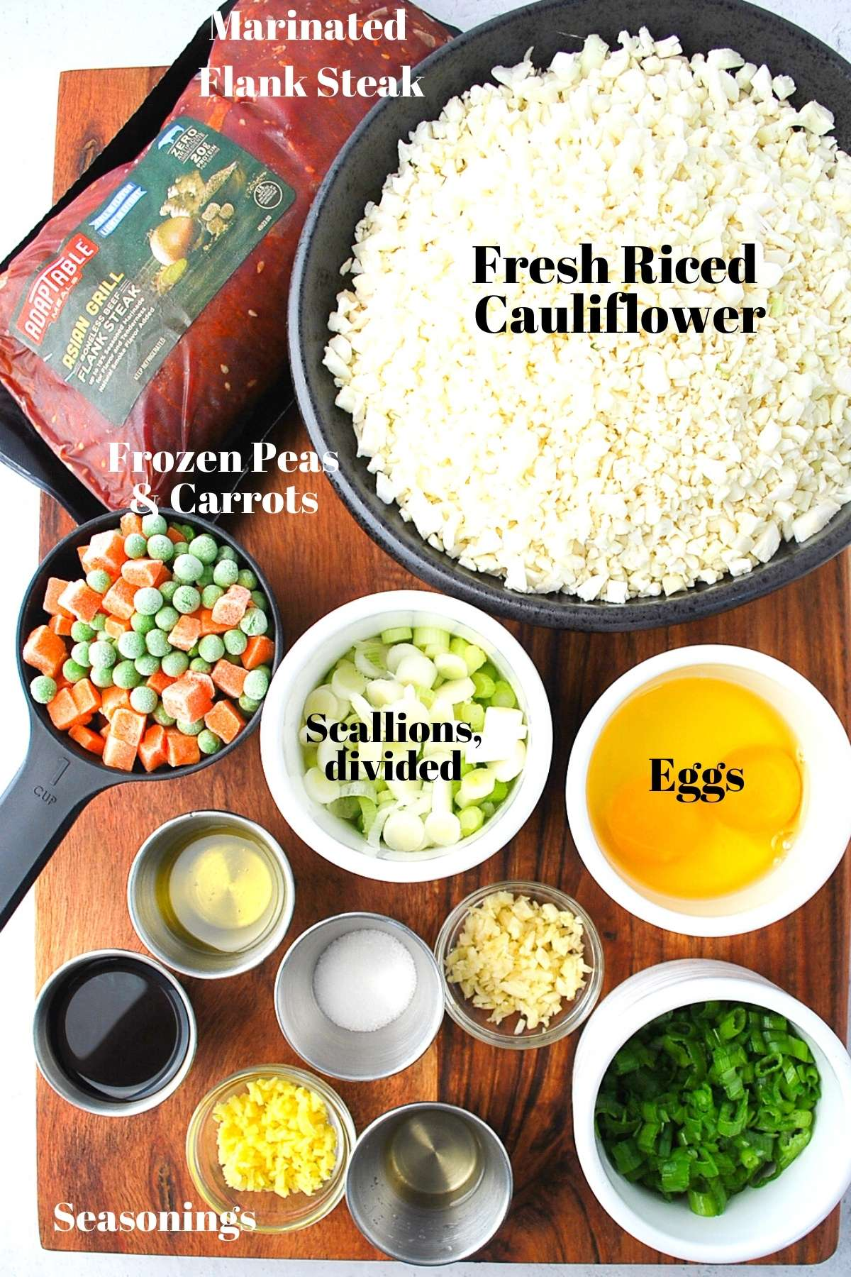 bowls of ingredients for making cauliflower fried rice and flank steak on a wooden board