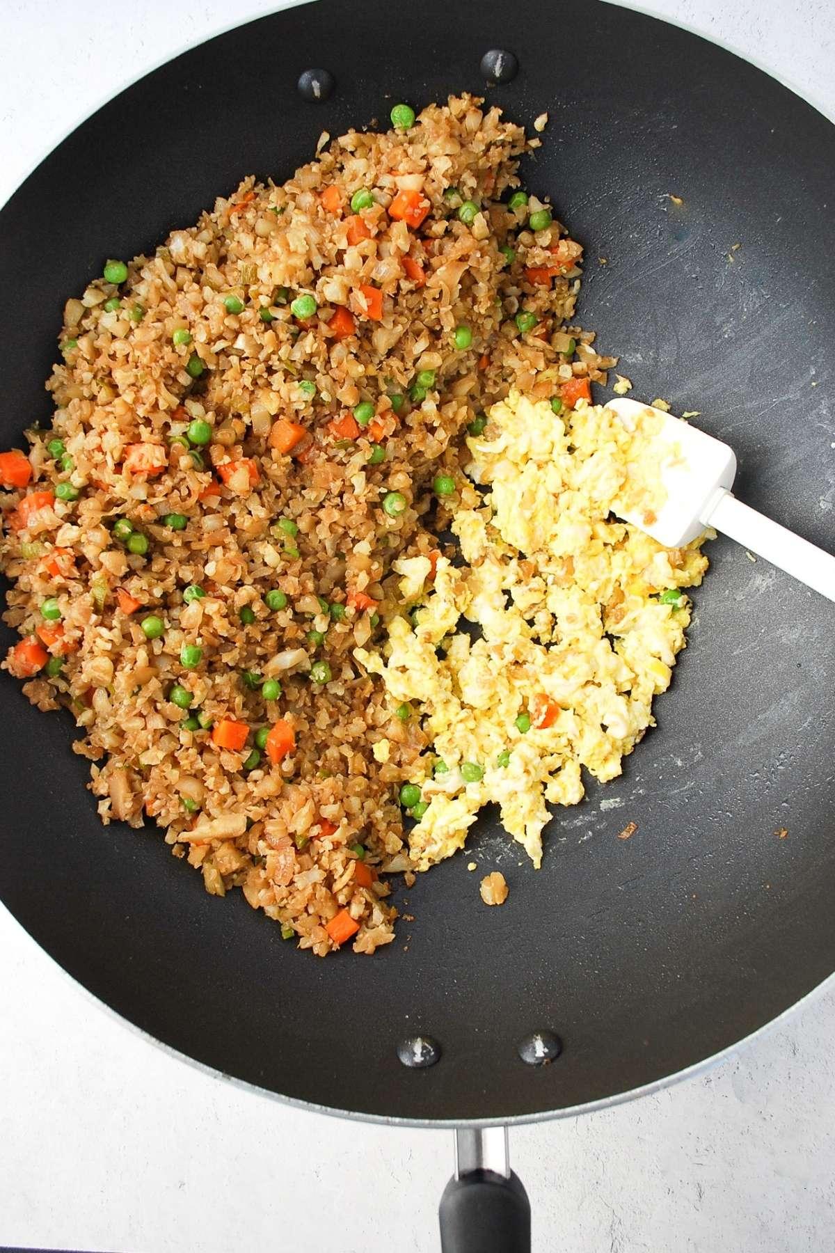 scrambling eggs next to cauliflower fried rice in a wok