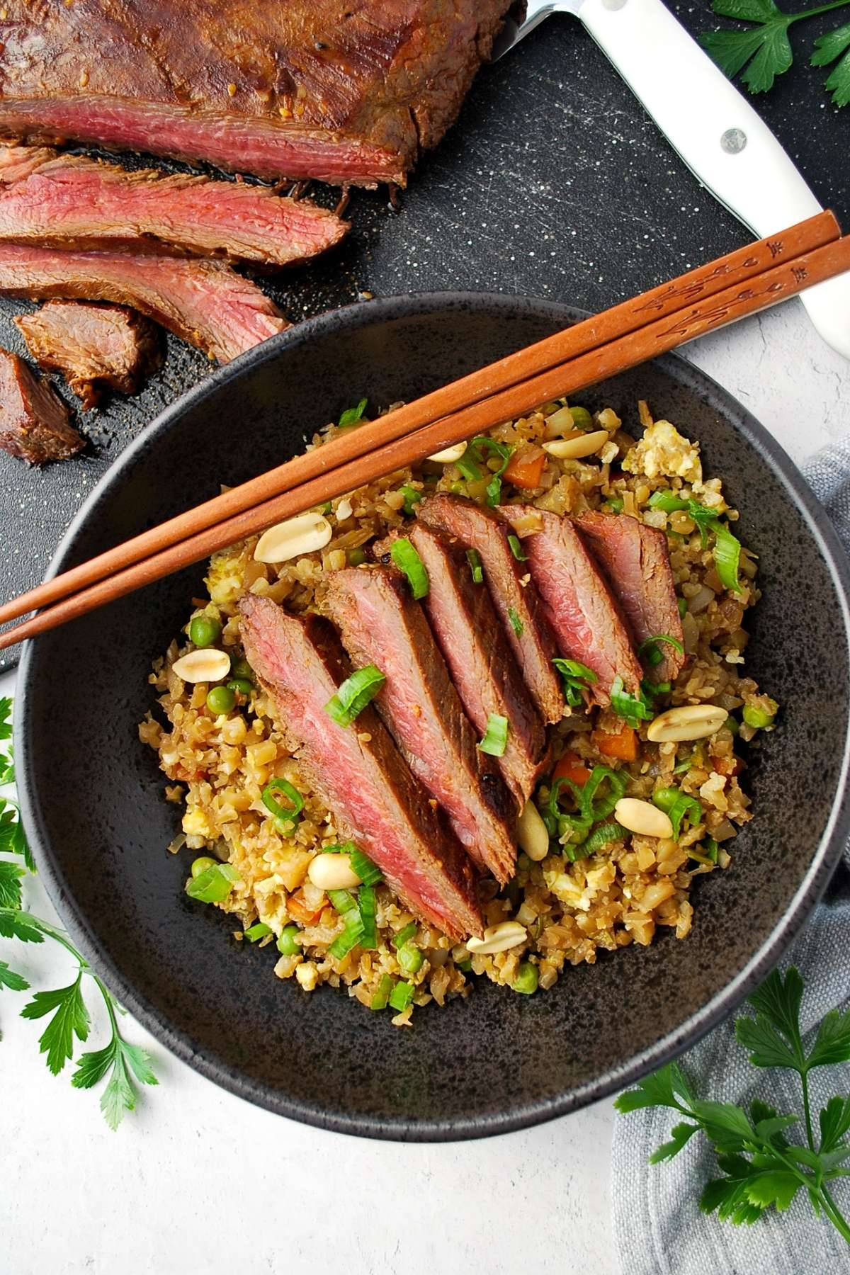 overhead photo of a bowl of cauliflower fried rice topped with sliced flank steak and chop sticks placed on top
