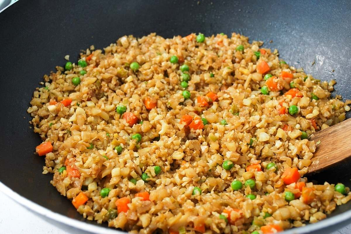 cauliflower fried rice with peas and carrots in a wok