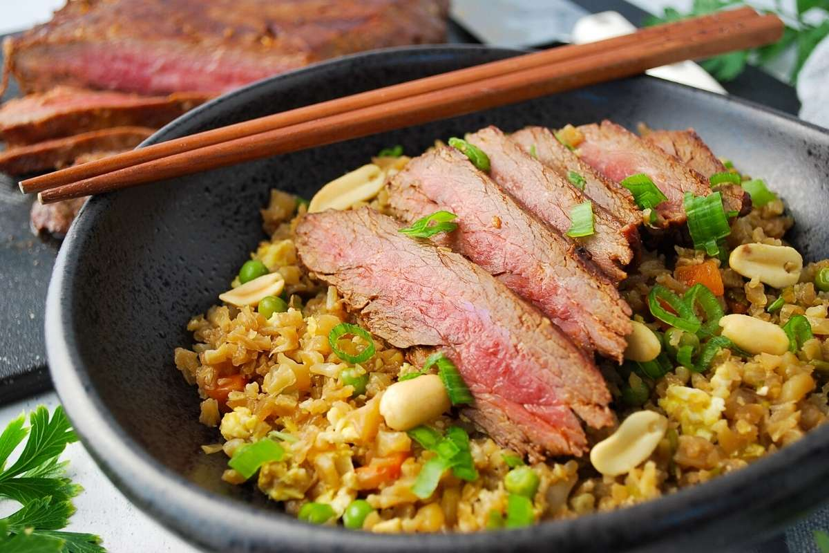 sliced flank steak on top of a bowl of cauliflower fried rice with chopped green onions and peanuts garnished on top