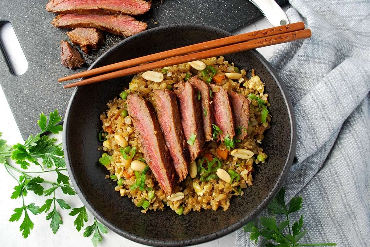 close up of a bowl of cauliflower fried rice topped with sliced steak and peanuts