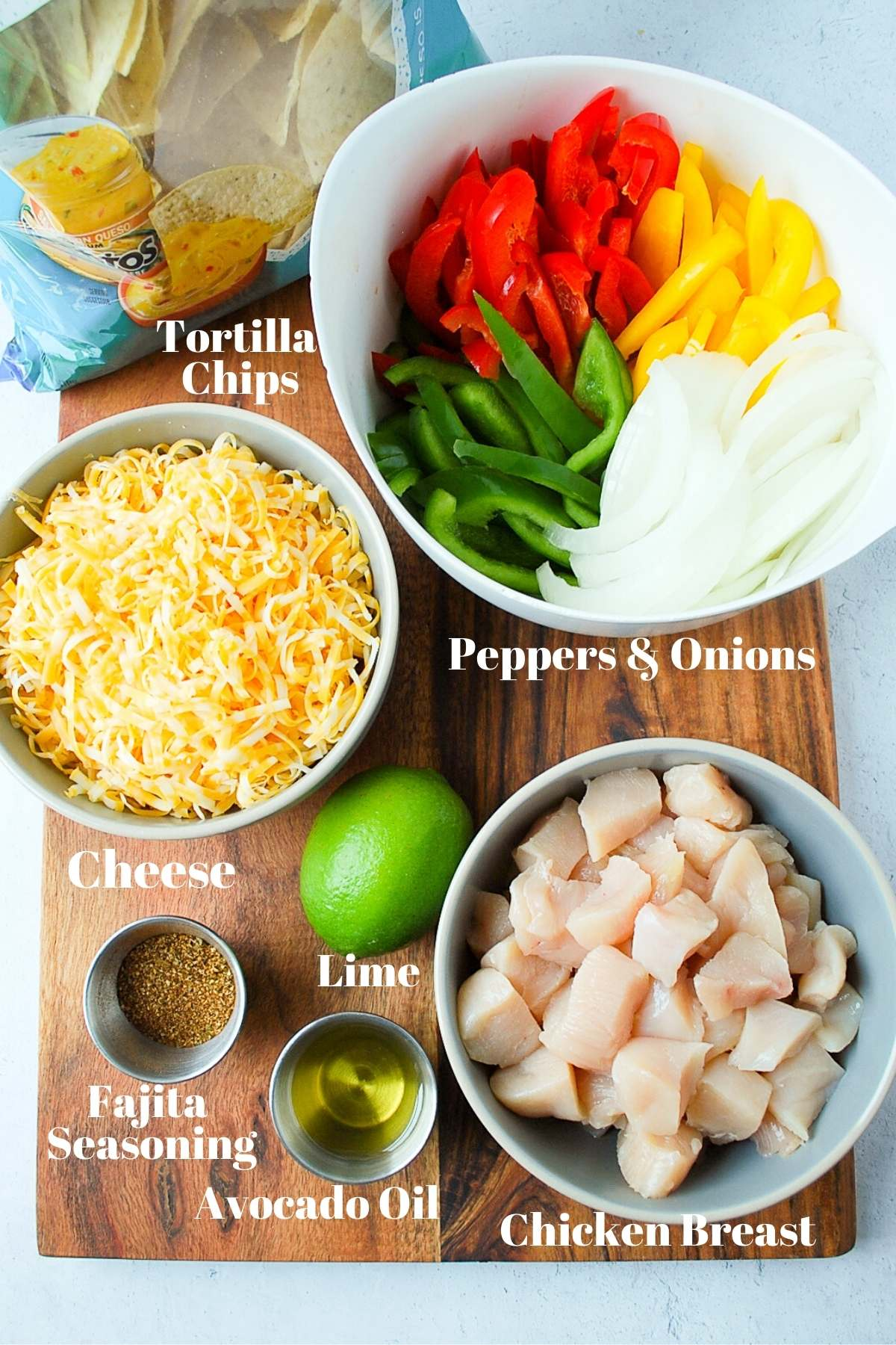 bag of tortilla chips, bowl of cheese, bowl of chicken, bowl of peppers and onions, a lime, oil, and fajita seasoning on a cutting board