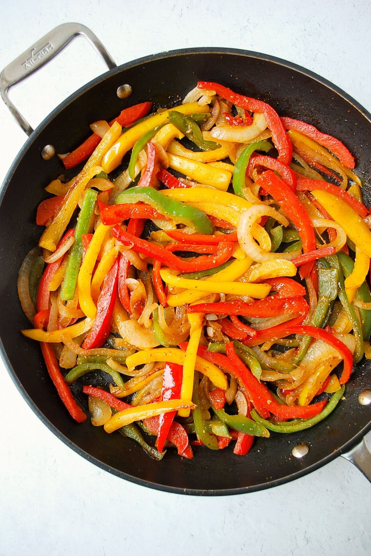cooked peppers and onions in a skillet